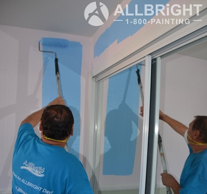 painter using roller brush to paint the interior of residential building